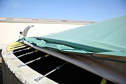 La bâche en PVC est posée sur des câbles en inox qui sont fixés tous les 40 cm à l'aide d'un piton et d'un tendeur, également en inox.